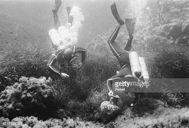 Two divers collect artefacts from the ocean floor during a navy expedition to Sicily, Italy, 26th May 1968.