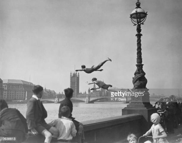 Two divers jumping off the Embankment into the River Thames in London near Westminster Bridge