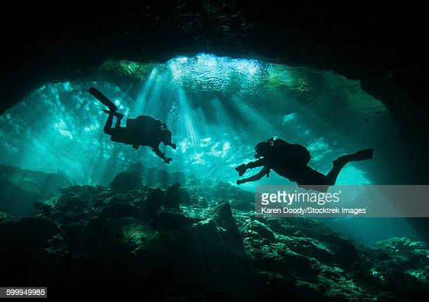 Two divers silhouetted in light at entrance to Chac Mool cenote, Mexico.