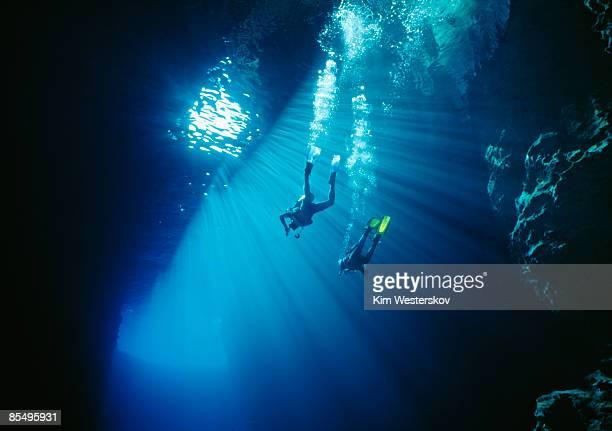 two divers swim thru sunbeams in sea cave, tonga   - tonga stock pictures, royalty-free photos & images