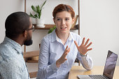 Two diverse businesspeople chatting sitting behind laptop in office