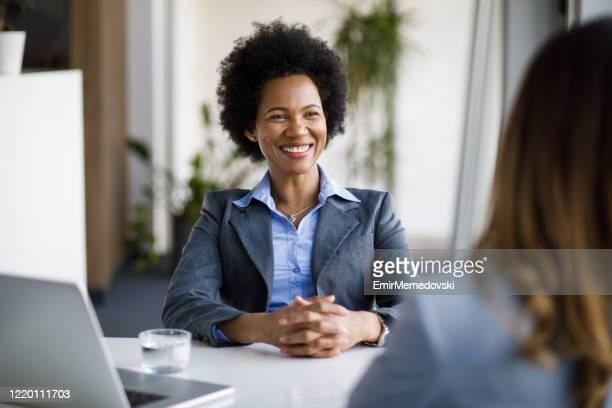 duas mulheres de negócios diversas conversando trabalhando juntas no escritório - sistema legal - fotografias e filmes do acervo