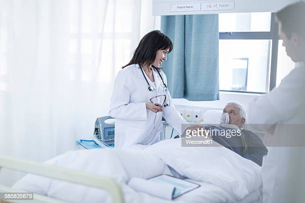 Two doctors and a patient in a hospital room