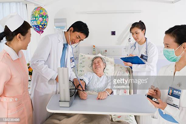 Two doctors and two nurses examining a female patient