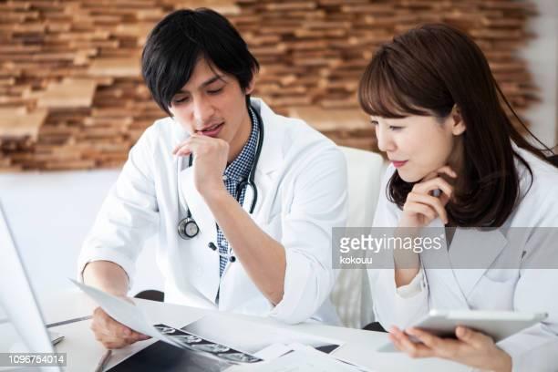 2 人の医師は、ドキュメントを見ています。 - 将校 ストックフォトと画像