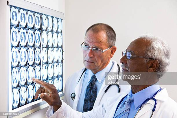 two doctors consulting on x-ray - gchutka stock pictures, royalty-free photos & images