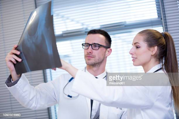 Two doctors discussing x-ray film