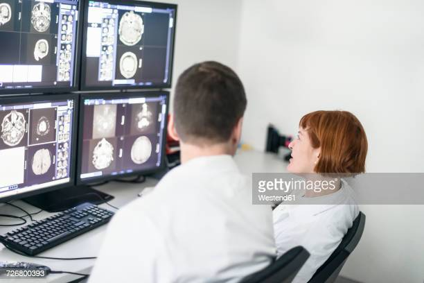 Two doctors discussing x-ray images on computer screen