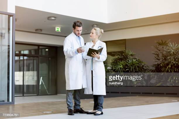 Two doctors having discussion, holding smartphone and diary