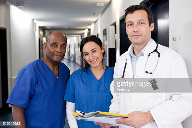 Two doctors in scrubs and a doctor in a lab coat in a hospital hallway