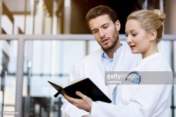 two doctors looking at diary - ジュニアドクター ストックフォトと画像