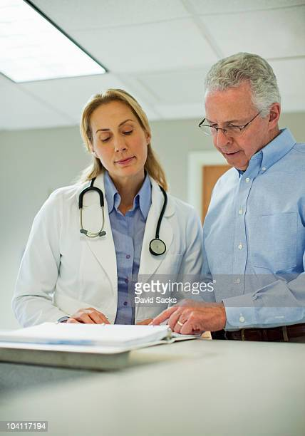 two doctors looking at medical chart - health2010 ストックフォトと画像