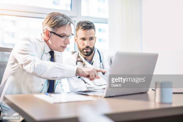 Two doctors looking at medical charts on laptop.