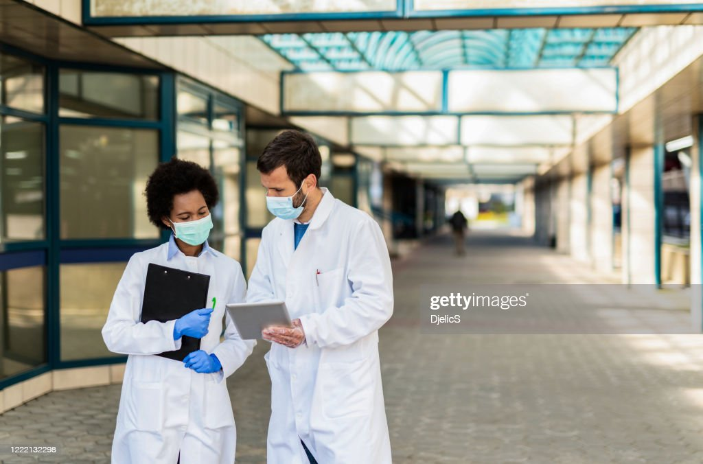 Two doctors looking at medical results on digital tablet. : Stock Photo