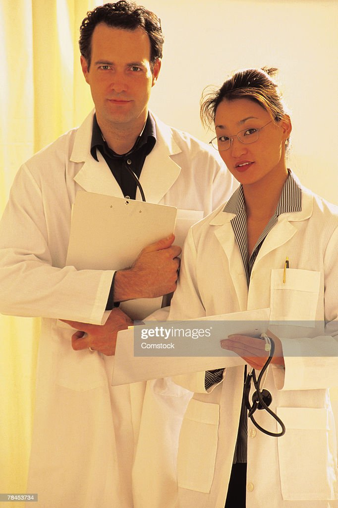 Two doctors posing with charts : Stockfoto