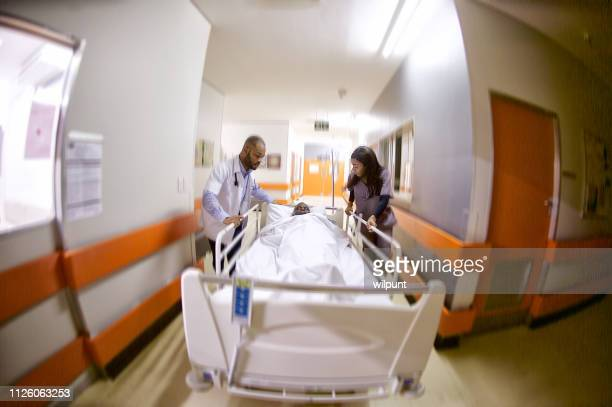 two doctors rushing an ill senior patient to intensive care warm - wide angle stock pictures, royalty-free photos & images