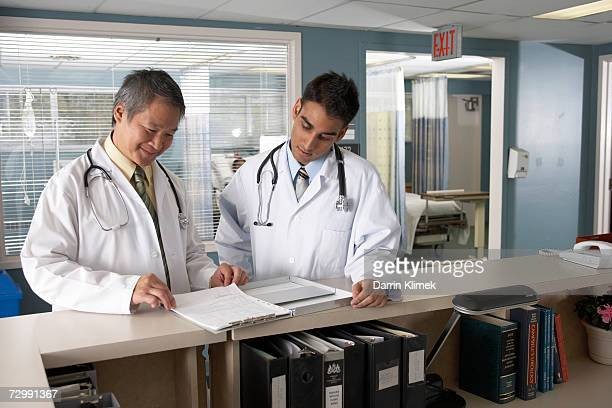 'Two doctors standing at reception area, looking at medical record'