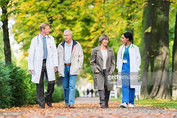 Zwei Ärzte mit altes Paar mit einem Fuß