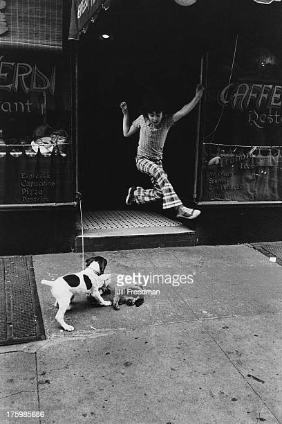 Two dogs and a child playing outside a cafe on Bleecker Street Greenwich Village New York City 1974