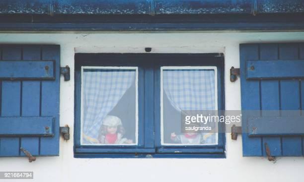 Two dolls in a window