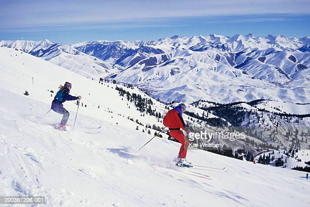 two downhill skiers on slope, sun valley, idaho, usa - sun valley idaho stock photos and pictures