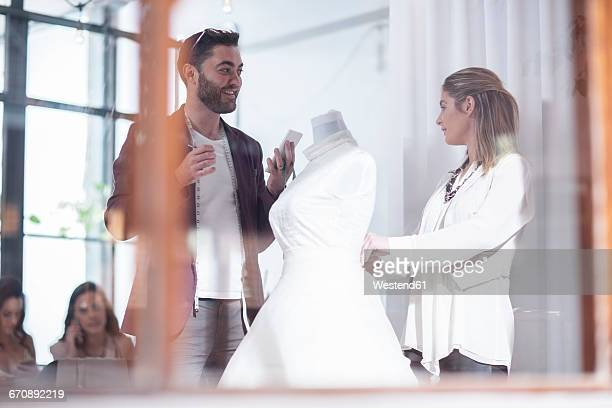 Two dressmakers with wedding dress discussing
