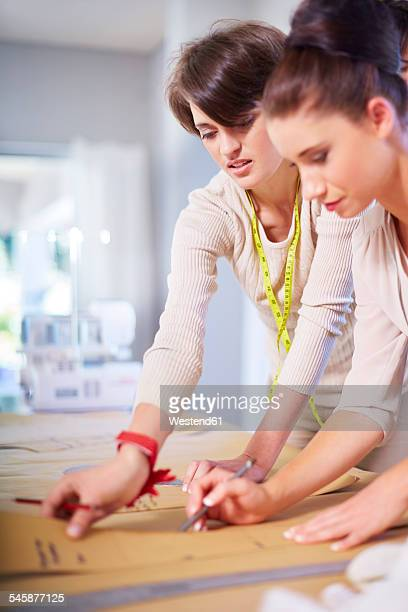 Two dressmakers working in tailor shop