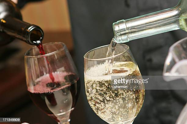 Two drinking glasses being filled with red and white wine
