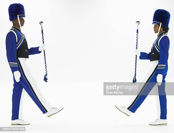 Two drum majors holding batons, marching toward one another, side view