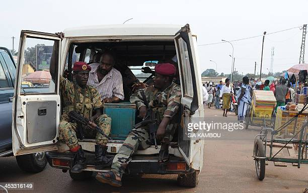 Two dsoldiers of the Central African Republic exrebel group Seleka escort the casket of a man to his funeral on December 3 2013 at the morgue of a...