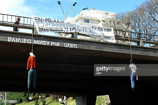Two dummies are hung from a bridge of a main avenue in Montevideo on November 2 placed in solidarity with Mexican civilian victims of the...