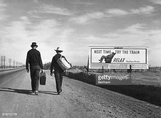 Two Dust Bowl refugees walk along a highway towards Los Angeles passing by a billboard imploring them Next Time Try the Train Relax
