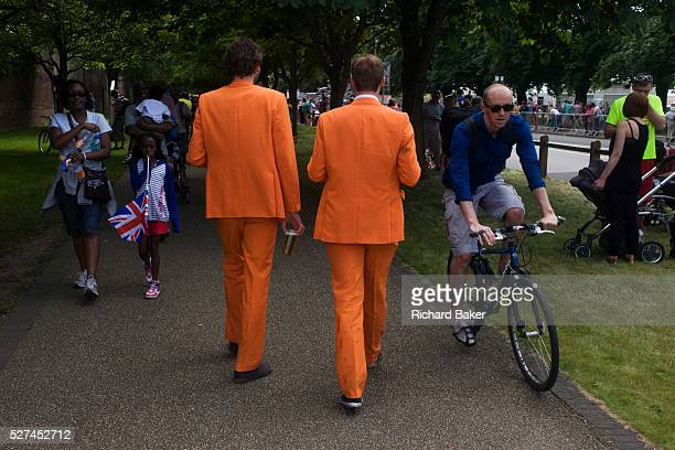 Two Dutch spectators wearing matching orange suits walk along an evenue in the former royal borough of Hampton Court palace of Henry the Eighth's...