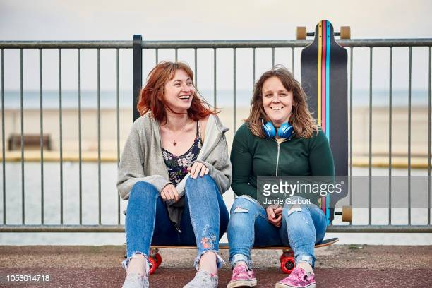 Two early 20's British female long boarders are sat together on a long board