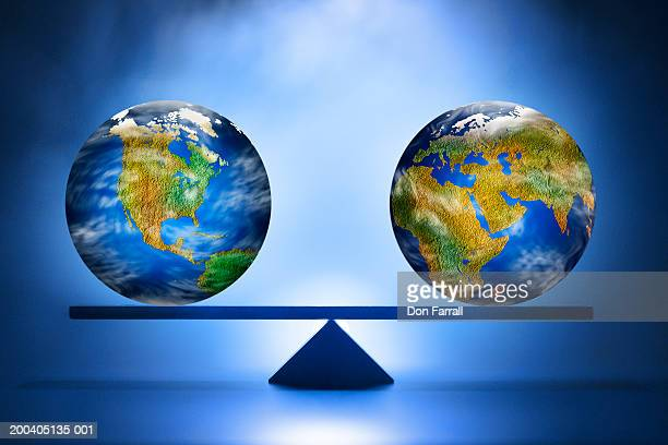 Two earth globes balancing on beam (Digital Composite)