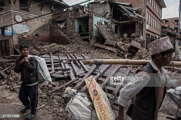 Two earthquake survivors carry goods past a building in Khokana a village dating back hundreds of years on the outskirts of Kathmandu on April 29...