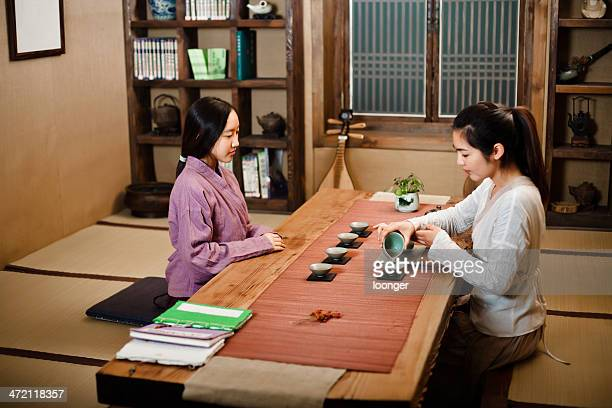 two east asian girl showing tea ceremony - tea room stock pictures, royalty-free photos & images