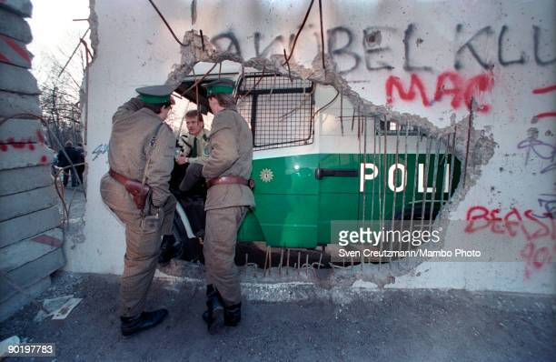 Two East German border guards talk to a West German police man through a hole in the Berlin Wall in February in Berlin Germany The wall that divided...