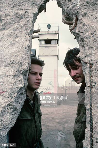 Two East German soldiers look out at West Berlin through a hole in the Berlin Wall