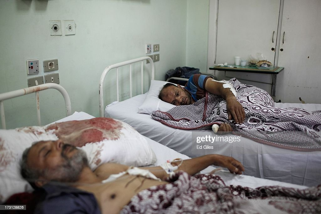 Two Egyptian men lie on beds at the Liltaqmeen al-Sahy Hospital in Cairo's Nasr City district, allegedly injured during a shooting at the site of a pro-Morsi sit-in in front of the headquarters of the Egyptian Republican Guard on July 8, 2013 in Cairo, Egypt. Egyptian health ministry officials are reporting at least 42 people were killed and more than 300 injured in the incident early on Monday morning, which allegedly occurred as supporters of deposed Egyptian President Mohammed Morsi attending the sit in were performing dawn prayer. The demonstrators were demanding the release of Morsi, who they believe is being held inside the Republican Guard headquarters.
