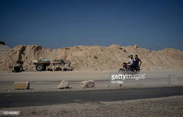 Two Egyptian men ride a motorcycle past a man working with a donkey cart in the city of El Arish, the capital of Egypt's restive North Sinai region,...