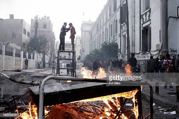 Two Egyptian protesters stand on top of a piece of furniture while riot police watch from a nearby rooftop during a protest following the...