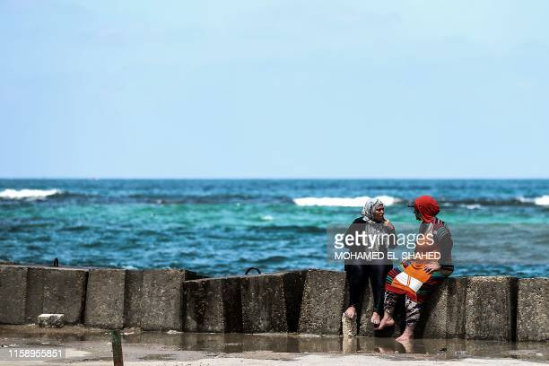 Two Egyptian women speak on a popular beach during summer vacations in the city of Alexandria, on August 01, 2019.
