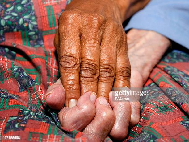 Two elderly hands grasped together in comfort and love
