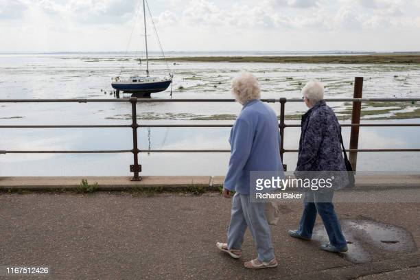 Two elderly ladies walk along the promenade where a single yacht sits upright in lowtide estuary mud at Old Leigh on 10th September 2019 in...
