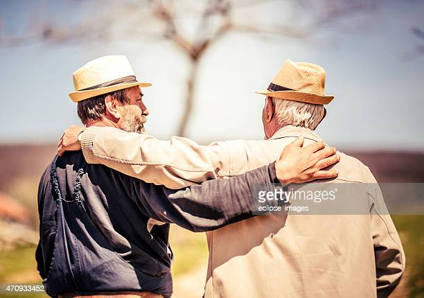 Two elderly male best friends in sideways embrace