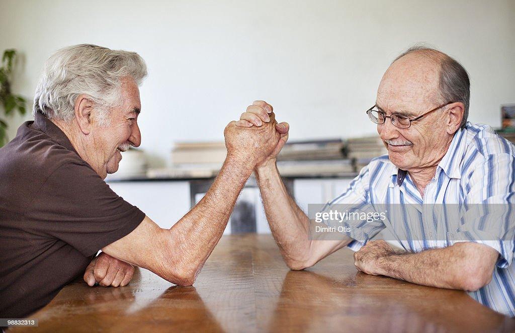 Two elderly men arm wrestling : Stock Photo