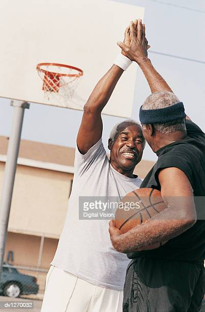 Two Elderly Men Giving High Five on a Basketball Court