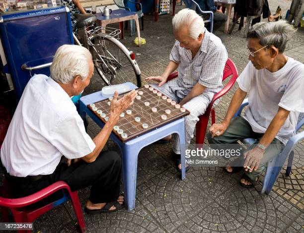 Two elderly men play Chinese chess on a street in Saigon as another man looks on.