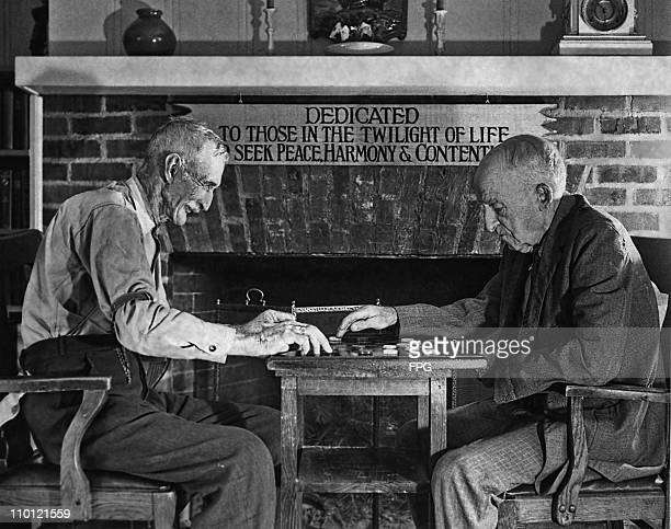 Two elderly men playing a game of draughts by a fireplace circa 1930 A sign behind them reads 'Dedicated to those in the twilight of life who seek...